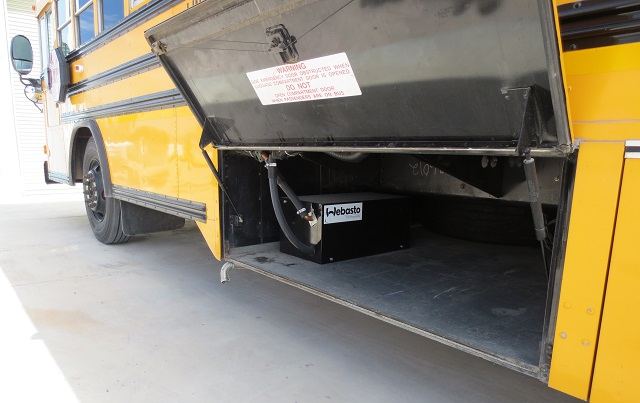 A fuel operated engine heater is installed in the luggage compartment of this school bus.
