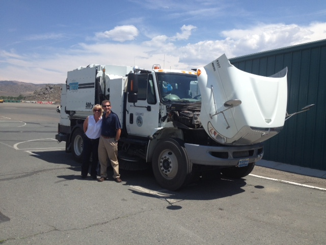 Two members of NDEP staff stand in front of Carson CIty's new Tymco street sweeper