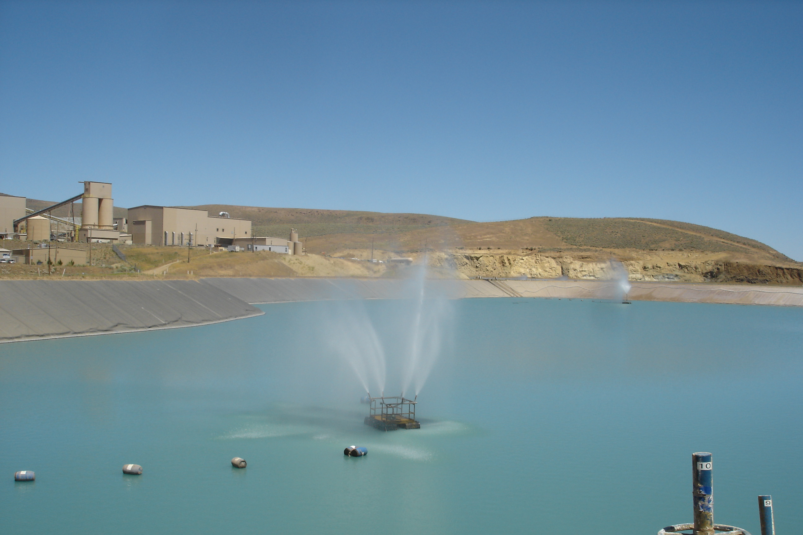 Tailings impoundment with evaporation sprinklers in operation.