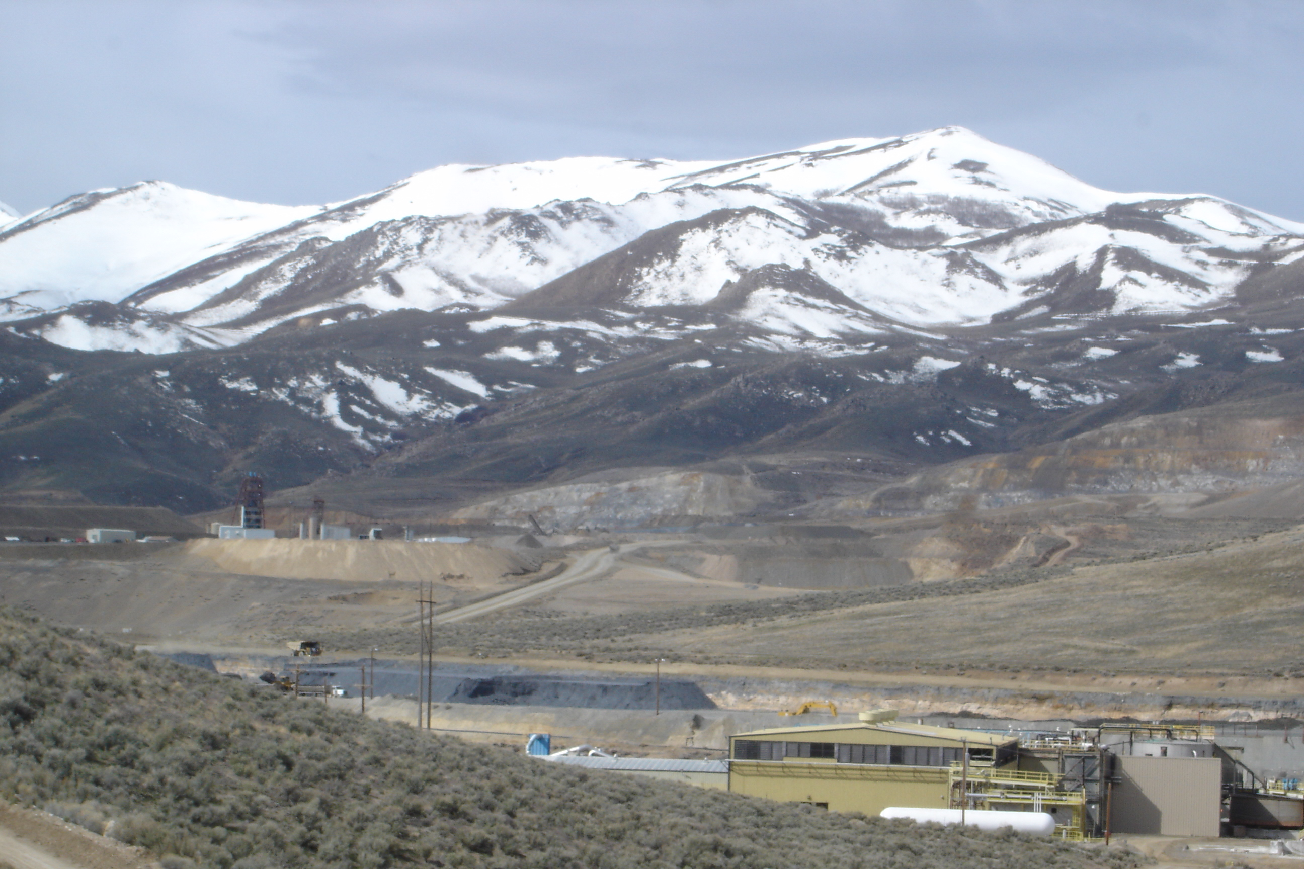 Snow covered mountains behind a mining operation.