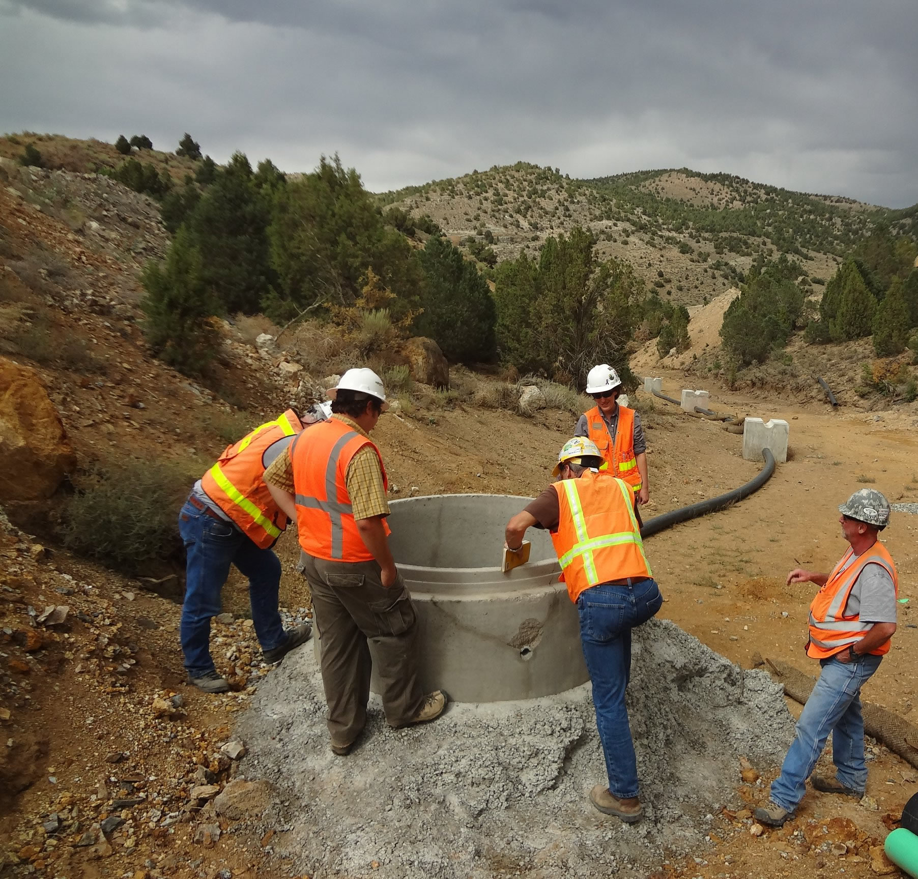 BMRR employees inspecting a sump near a mine site.