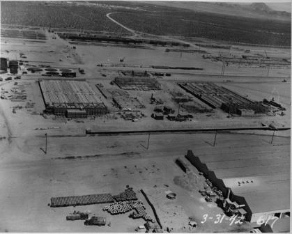 1942-03-31 Aerial view of several buildings under construction at the BMI plant. The image shows a portion of the chlorine plant including brine preparation tanks and footings (upper left) steel framing of the cell renewal building (center) chlorine cell buildings (center right and left) and drying, cooling, and liquefaction units between the cell buildings. The temporary brick grinding building is in the lower right.